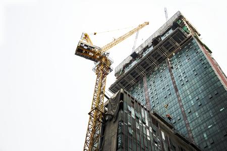 Photo pour Crane and building construction site against blue sky.Under construction concept - image libre de droit