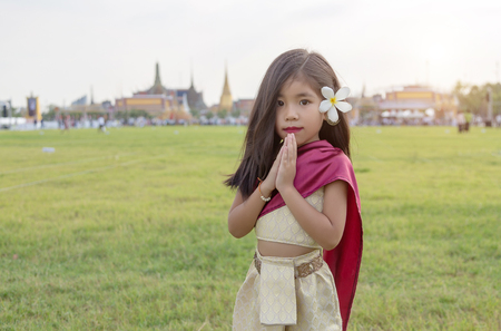 Photo for asian Thai kids with Thai tradition dress. greeting action call Wai and said Sawasdee with Royal park and temple destination of Bangkok Thailand on background - Royalty Free Image