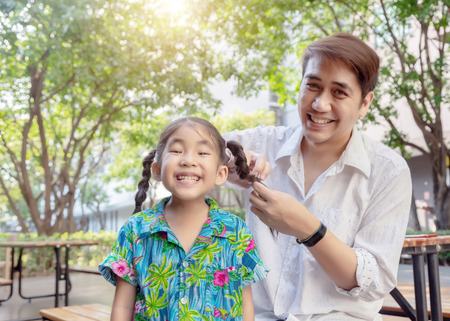 Photo pour stepfather concept daddy love daughter do pigtail hair for kid at park in morning. Lovely moment of family. - image libre de droit