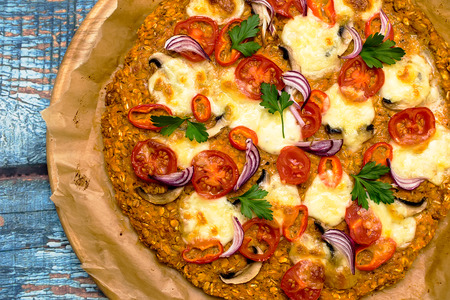 Photo pour Pizza with blat of sweet potato and oat seeds, garnished with mushrooms, onions, mozzarella and cherry tomatoes - image libre de droit
