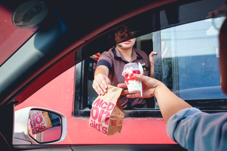 Photo pour Bangkok, Thailand - Mar 4, 2017: Unidentified customer receiving hamburger and ice cream after order and buy it from McDonald's drive thru service, McDonald's is an American fast food restaurant chain - image libre de droit