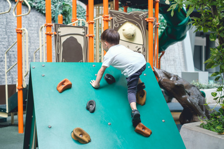 Photo for Cute Asian 2 - 3 years old toddler child having fun trying to climb on artificial boulders at indoor playground, Little boy climbing up a rock wall, Hand & Eye Coordination, Motor Skills development - Royalty Free Image