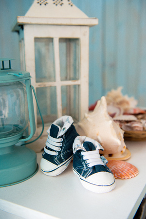 Childrens jeans sneakers in the sea interior against the background of seashells.