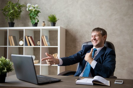 Photo pour Happy excited young businessman sitting on workplace and celebrating success. - image libre de droit
