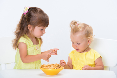 Photo pour Two cute little girls sisters in yellow t-shirts eating cereal flakes at the table isolated on white background. - image libre de droit