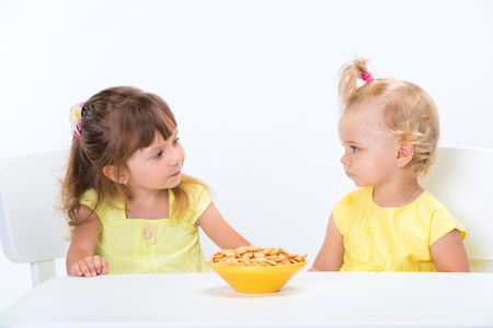 Photo for Two cute little girls sisters in yellow t-shirts eating cereal flakes at the table isolated on white background. - Royalty Free Image