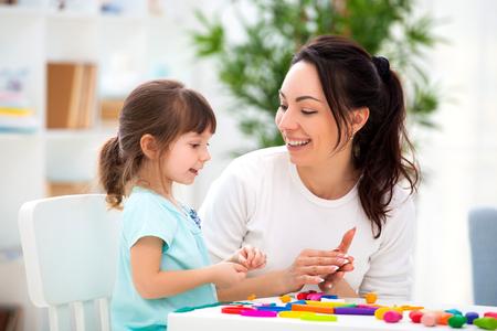Photo pour Smiling mother helps a little daughter to sculpt figurines from plasticine. Children's creativity. Happy family. - image libre de droit