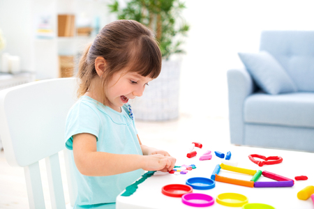 Photo for Smiling little beautiful girl sculpt new house of plasticine. Children creativity. Happy childhood. Housewarming dreams. - Royalty Free Image
