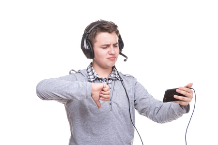 Photo pour Schoolboy guy with headphones playing on mobile phone. Teenager happy screams . Young man won an online game on a smartphone. Cheers to the winner. - image libre de droit