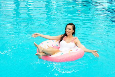 Photo pour Beautiful young woman in a bathing suit relaxing on inflatable donut in swimming pool. Enjoying summer and having fun. Vacation mood - image libre de droit