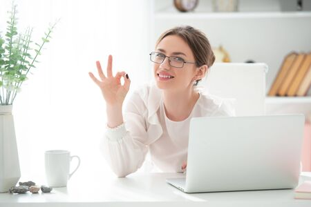 Photo for Smiling young woman in the office is very happy from a successful order and shows OK sign. Good job, victory. Emotions of joy overwhelm. - Royalty Free Image