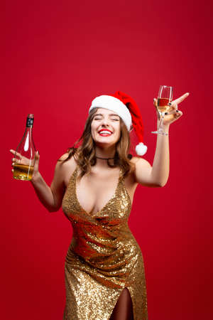 Photo pour Girl in a gold dress and a Christmas hat drinks champagne on a red background. Concept of a New Year holiday party - image libre de droit