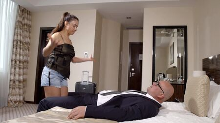 Photo pour Rich businessman in a suit lying on the bed at the hotel looking at his mistress, a pleasure pastime - image libre de droit