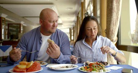 Photo pour nice couple enjoys eating salads sitting near window in cafe - image libre de droit