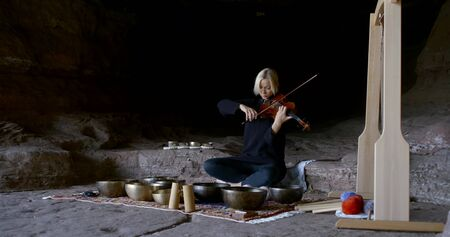 A blonde woman sits on a stone surface and conducts Tibetan practice, sound therapy, massage with sound vibrations, plays the violin, there are bowls around her.
