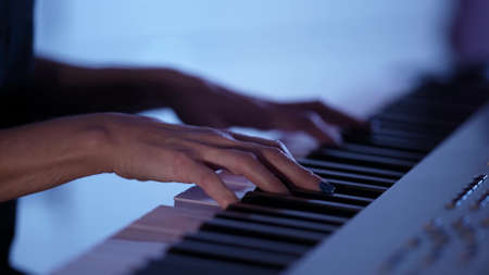 Photo pour female musician is playing electric piano at home at darkness, closeup of hands over keys - image libre de droit