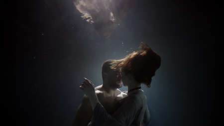 Photo pour embrace underwater, loving pair is hugging in darkness and deepness - image libre de droit