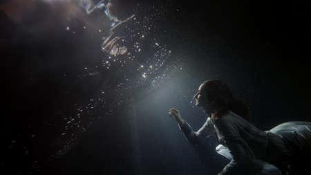 Photo pour beautiful young woman is floating under water surface, magic subaquatic slow motion shot - image libre de droit