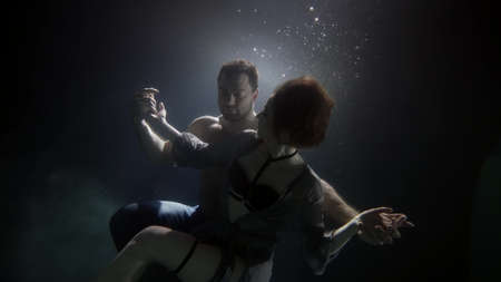 Photo pour muscular man is holding graceful woman in hugs underwater, tenderness and love of young people - image libre de droit