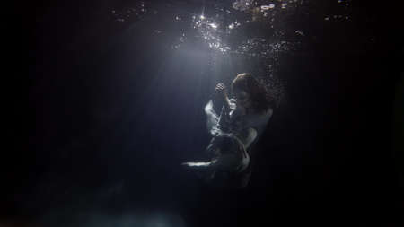 Photo pour fragile and graceful woman is floating in dark water of swimming pool, mysterious subaquatic shot - image libre de droit