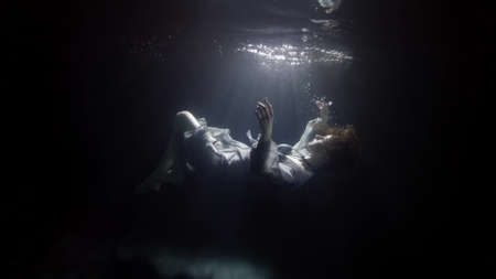 Photo pour silhouette of sinking woman underwater, floating and diving under surface of dark pool - image libre de droit