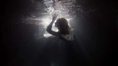 Photo pour mystic female figure underwater, lady is floating inside water in sea or ocean, nymph or fairy - image libre de droit