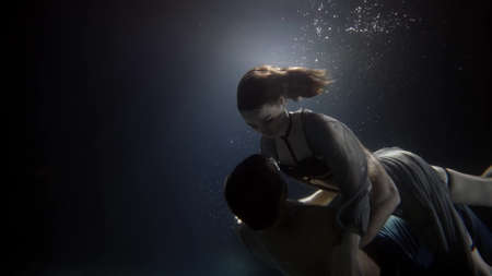 Photo pour young man and woman are swimming underwater and embracing, romantic and love of couple - image libre de droit
