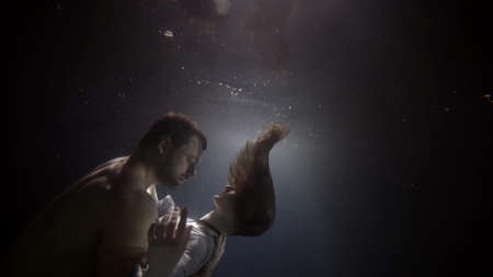 Photo pour brawny man and slender woman are embracing underwater, dark depth and stream of light, romantic and passion - image libre de droit
