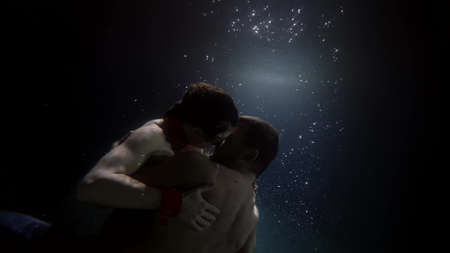 Photo pour romantic couple inside dark water of ocean or pool, embracing man and woman, love and tenderness - image libre de droit