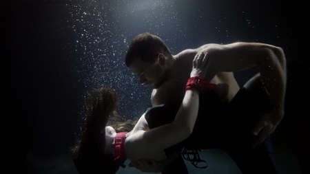 Photo pour dancing pair inside water of swimming pool, man is hugging slender sexy woman and looking at camera - image libre de droit