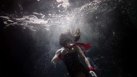 Photo pour passionate woman with whip is floating inside clear water, underwater slow motion shot - image libre de droit