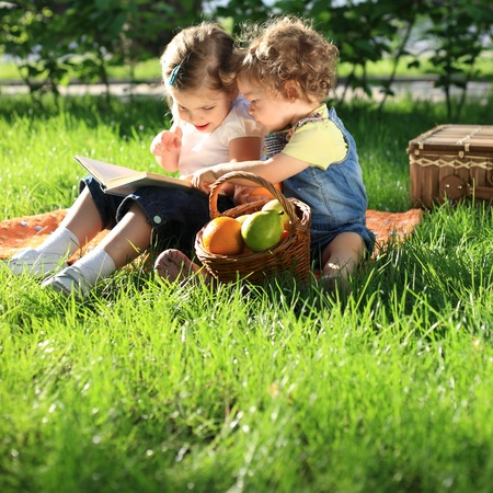 Children reading the book on picnic in summer park