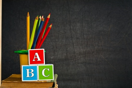Photo for ABC and multicolored pencil on old textbook against blackboard in class. School concept - Royalty Free Image