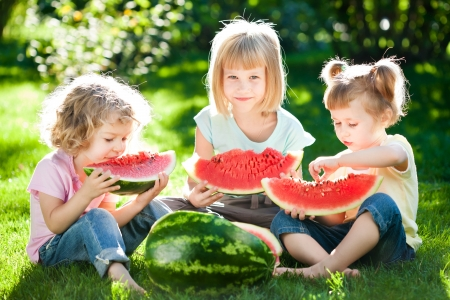 Foto per Group of happy children eating watermelon outdoors in spring park - Immagine Royalty Free