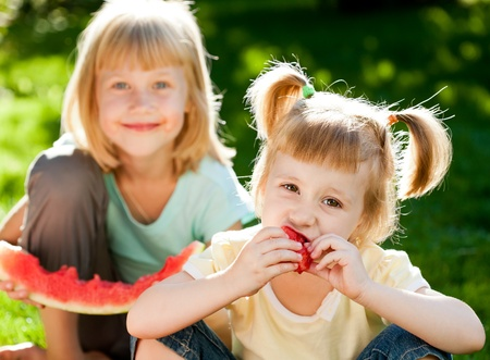 Photo for Happy children eating watermelon outdoors in spring park - Royalty Free Image