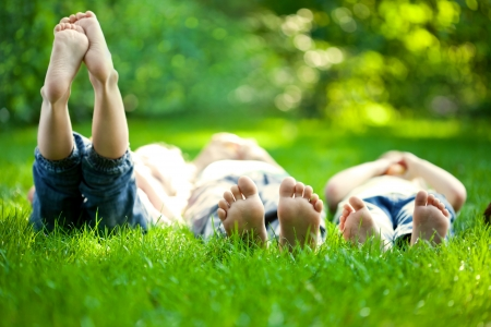 Foto de Group of happy children lying on green grass outdoors in spring park - Imagen libre de derechos