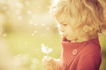 Beautiful child blowing away dandelion flower in spring