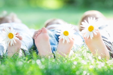 Group of happy children lying outdoors against green spring background