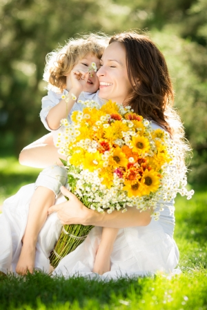 Foto de Happy child and woman with bouquet of spring flowers sitting on green grass. Mother`s day concept - Imagen libre de derechos