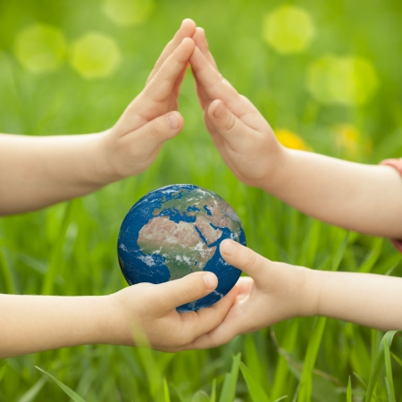 Photo pour Earth in children s hands against green spring background  Elements of this image furnished by NASA - image libre de droit
