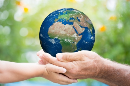 Child and senior man holding planet Earth in hands against green spring background.