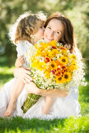 Happy child giving big bouquet of spring flowers to woman for mother`s day の写真素材