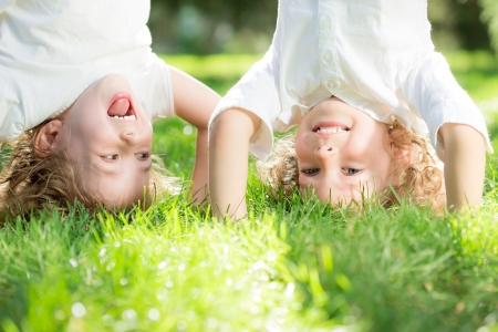 Photo pour Happy children standing upside down on green grass in spring park. Healthy lifestyles concept.  - image libre de droit
