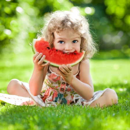 Happy child with big red slice of watermelon sitting on green grass in summer park  Healthy eating concept