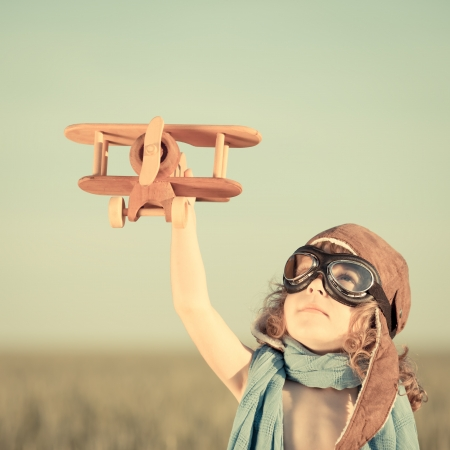 Happy kid playing with toy airplane against blue summer sky background