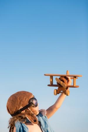 Foto de Happy kid playing with toy airplane against blue summer sky background   - Imagen libre de derechos