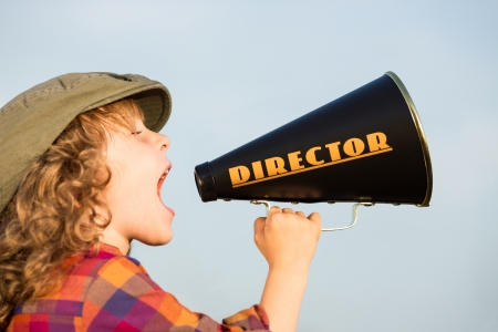 Kid shouting through director vintage megaphone