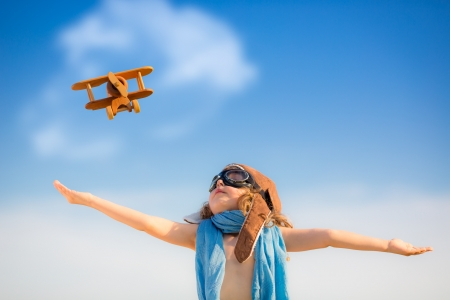 Foto per Happy kid playing with toy airplane against blue summer sky background - Immagine Royalty Free