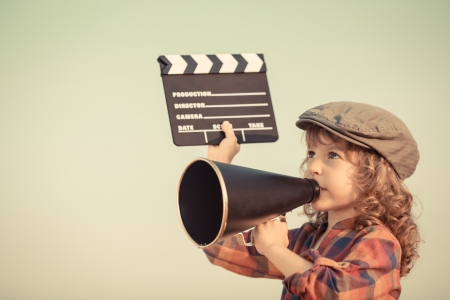 Kid holding clapper board and shouting through vintage megaphone  Cinema concept  Retro style