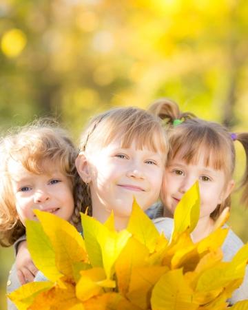 Foto de Happy children with maple leaves in autumn park - Imagen libre de derechos